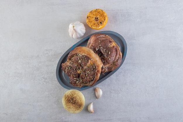 Carne fresca affettata con verdure fresche poste su un tavolo di pietra.