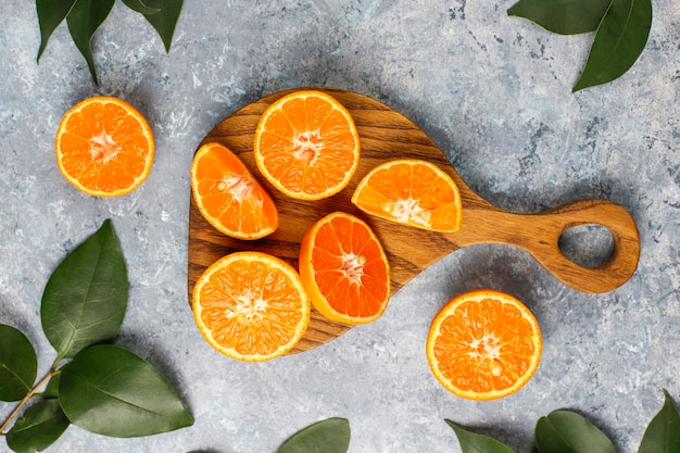 Fresh sliced oranges on cutting board on concrete surface