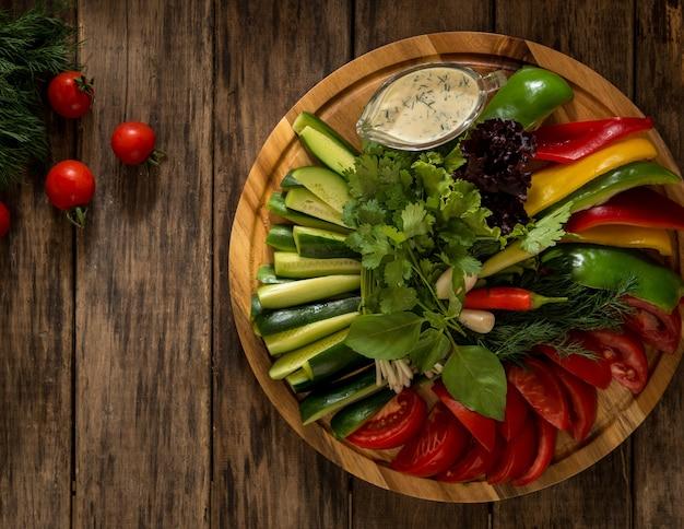 둥근 쟁반에 있는 신선한 야채 조각 나무 표면에 있는 다양한 야채