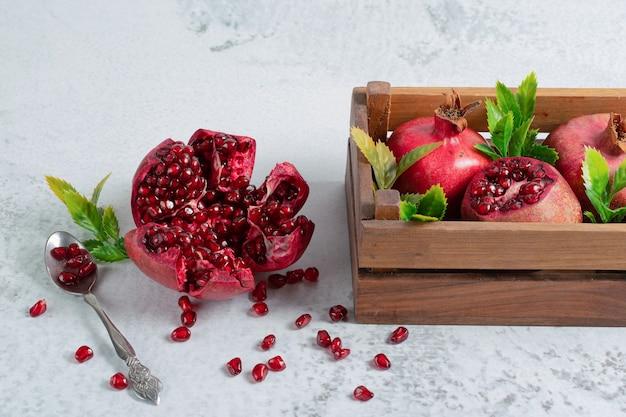 과일 활과 함께 회색 표면에 신선한 얇게 썬 석류.