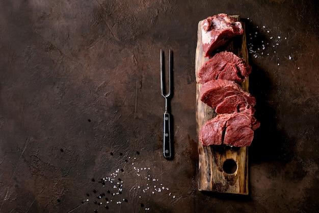 木の板にステーキ用にスライスした生の牛ヒレ肉を、金属の肉フォーク、塩、コショウでこげ茶色のテクスチャー面に乗せたもの食品料理の背景コンセプト。トップ ビュー、フラット レイアウト、コピー スペース