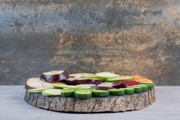 新鮮なスライスした生野菜を木片に。高品質の写真