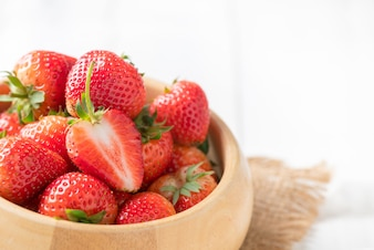 Fresh sliced Red berry strawberries in wood bowl on white wood background, diet fruits concept