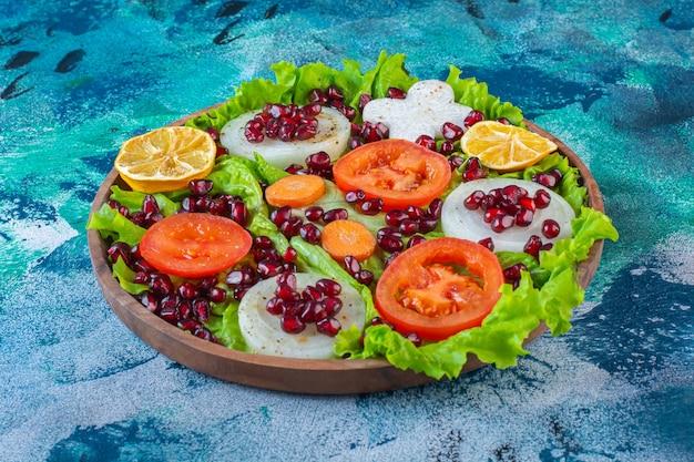 Свежие, нарезанные различные овощи на деревянной тарелке