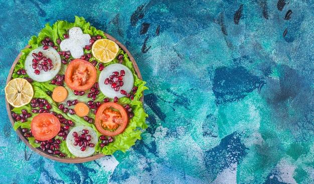 Varie verdure fresche e affettate su un piatto di legno