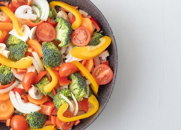 Свежие нарезанные овощи на сковороде и белом фоне с копией пространства справа