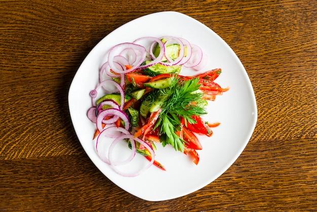 Свежие нарезанные овощи с зеленью на белой тарелке