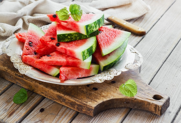 Fresh sliced watermelon in a metal bowl wooden