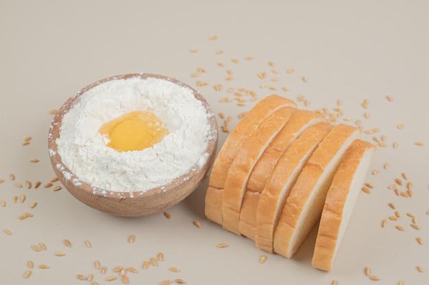 小麦粉でいっぱいの木製のボウルと新鮮なスライスした白パン