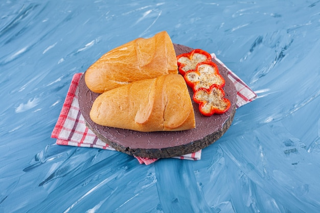 Fresh sliced white bread on wooden piece and pepper slices.