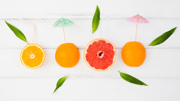Fresh slices of citruses with decorative umbrellas and green leaves