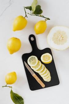 Fresh slices of lemon on a black chopping board flatlay