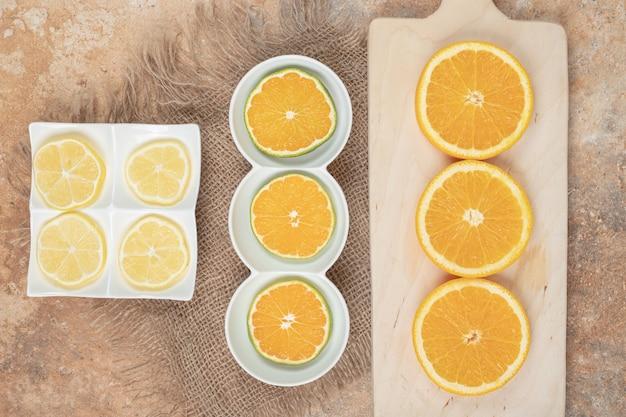 Свежие дольки апельсина и лимона на различных тарелках.