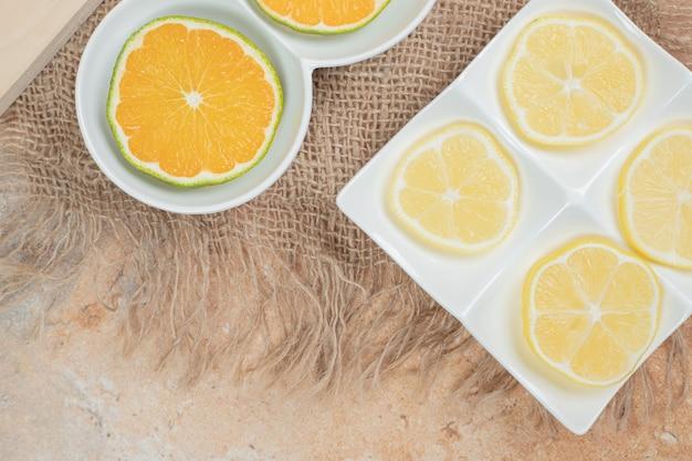 다양 한 접시에 오렌지와 레몬의 신선한 조각.