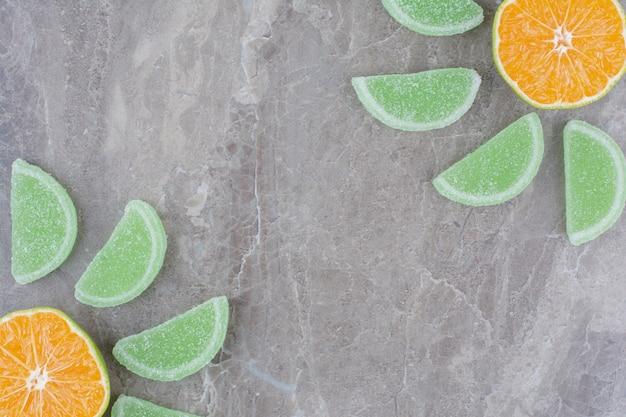 Свежие дольки апельсина со сладким мармеладом на мраморном фоне.