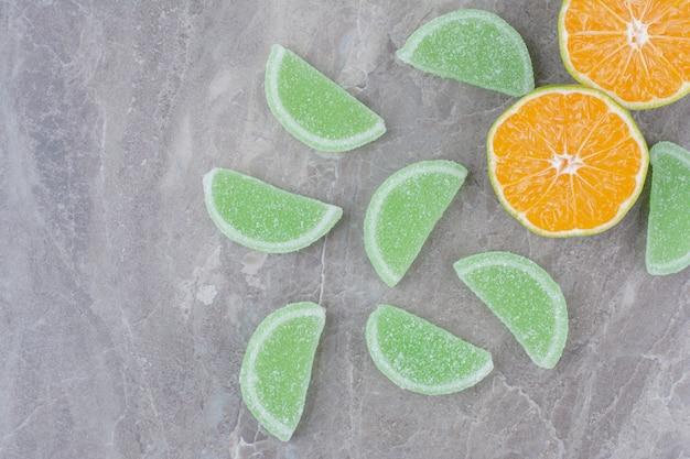 大理石の背景に甘いマーマレードとオレンジの新鮮なスライス。