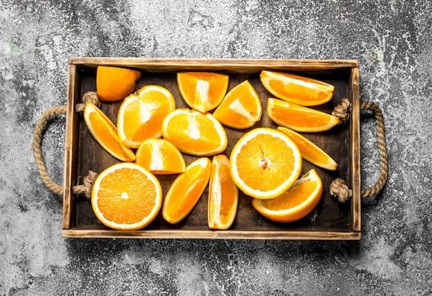 Свежие дольки апельсинов в деревянном подносе на деревенском фоне