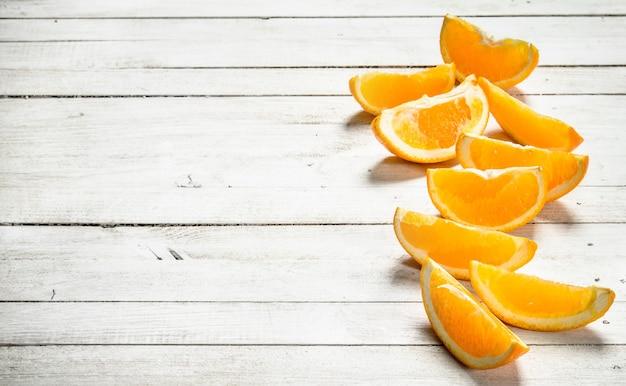 Свежие дольки апельсинов на белом деревянном столе