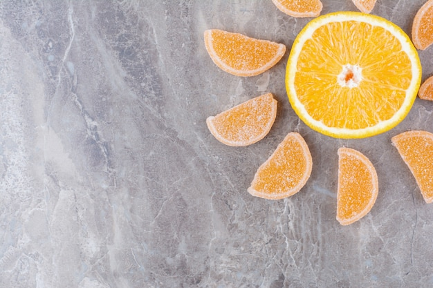 Fette fresche di arancia con marmellate dolci su sfondo marmo.