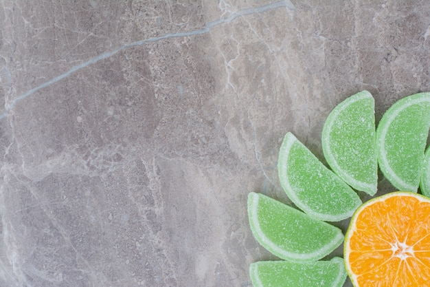Fresh slices of orange with sweet marmalades on marble background.