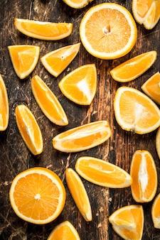 Свежие апельсины дольками на деревянном фоне