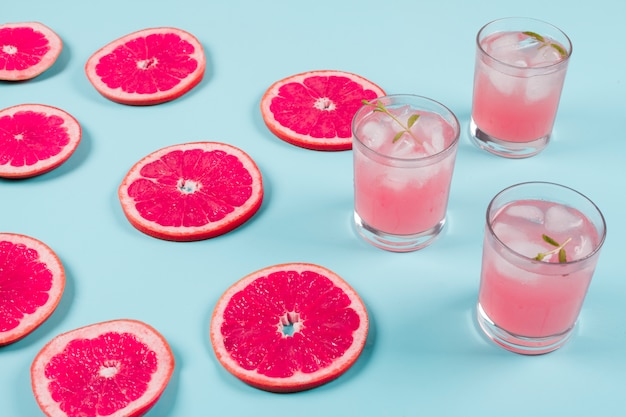 Fresh slices of ripe grapefruit and cold juice on blue background