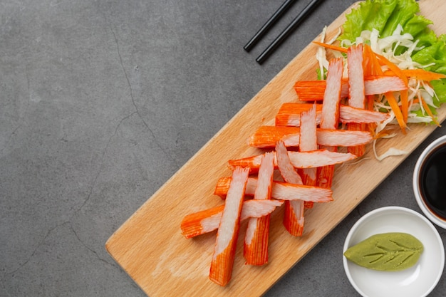 Fresche diapositive di bastoncini di granchio con wasabi e salsa