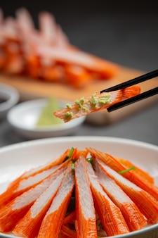 Fresche diapositive di bastoncini di granchio con wasabi e salsa di soia