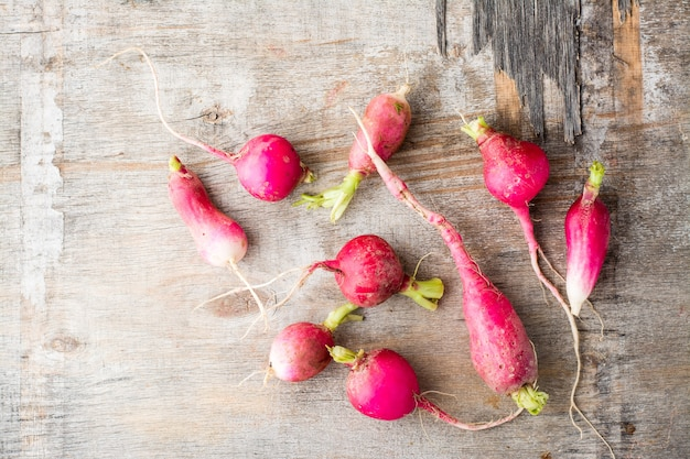 Fresh slightly overgrown radishes on a wooden table. rustic style. top view