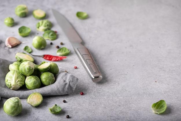 灰色のテーブル、上面図にハーブとピーマンと新鮮な小さな芽キャベツ