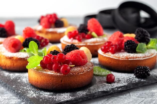 テーブルの上にラズベリー、スグリ、ブラックベリーが入った新鮮な小さな自家製フルーツパイ