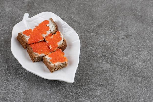 회색 표면 위에 하얀 접시에 신선한 작은 샌드위치.