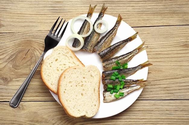 Свежие копченые шпроты и хлеб деревянные на столе