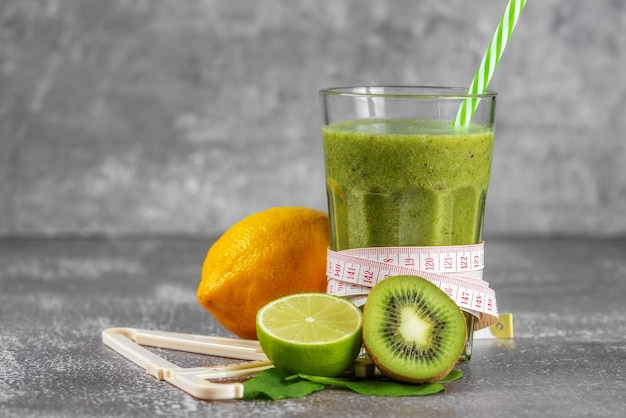 회색 콘크리트 배경에 과일로 둘러싸인 센티미터와 캘리퍼스가 옆에있는 키가 큰 유리 잔에 신선한 스무디 음료. 적절한 영양, 체중 감소의 개념