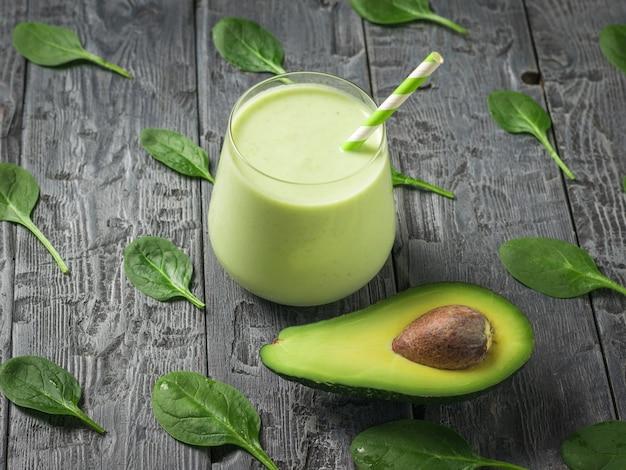 시금치 잎이 있는 나무 테이블에 아보카도가 든 유리잔에 신선한 스무디. 피트니스 제품. 다이어트 스포츠 영양.