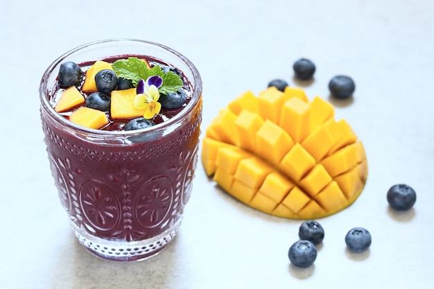 Fresh smoothie with mango and blueberry topping