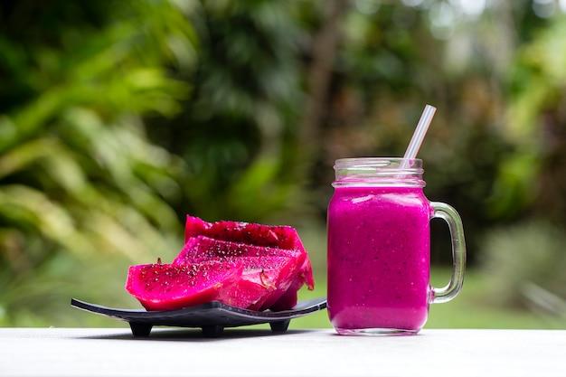 Fresh smoothies from a dragon fruit, banana, mango and papaya in glass mug