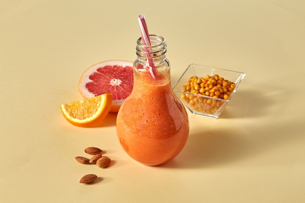 にんじん、オレンジ、グレープフルーツ、アーモンド、シーバックソーンと紙のオレンジ色の背景のガラスの新鮮なスムージー。ビタミンドリンクのコンセプト