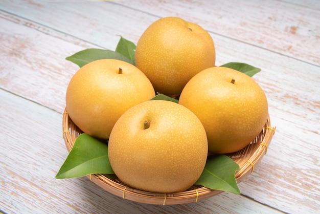 대나무 바구니에 신선한 눈 배 과일 나무 배경에 바구니에 신선한 나시 배 과일