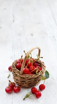 Свежая вишня в корзине на деревянном столе