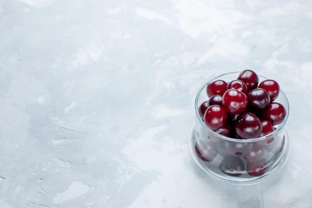 Ciliege acide fresche all'interno di una piccola tazza di vetro sulla scrivania bianca chiara, foto di vitamine delle bacche acide di frutta