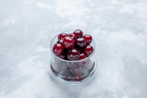 明るい白い机の上の小さなガラスのカップの中の新鮮なサワーチェリー