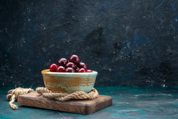 Свежая вишня внутри тарелки с веревками на темном