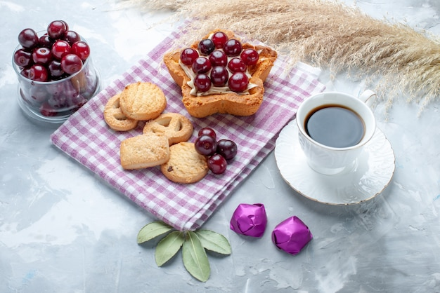 Fresh sour cherries inside plate with star shaped creamy cake tea and cookies on light desk, fruit sour cake biscuit
