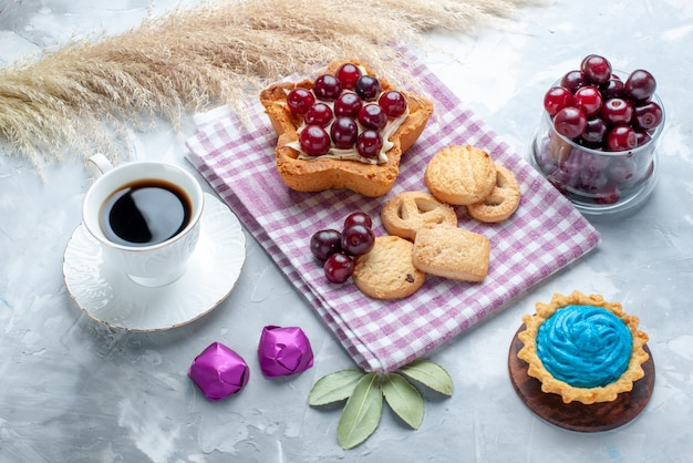 Fresh sour cherries inside plate with star shaped creamy cake tea and cookies on light