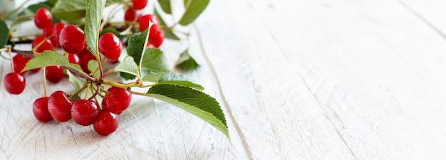 白い木製のテーブルの上の新鮮なサワーチェリー