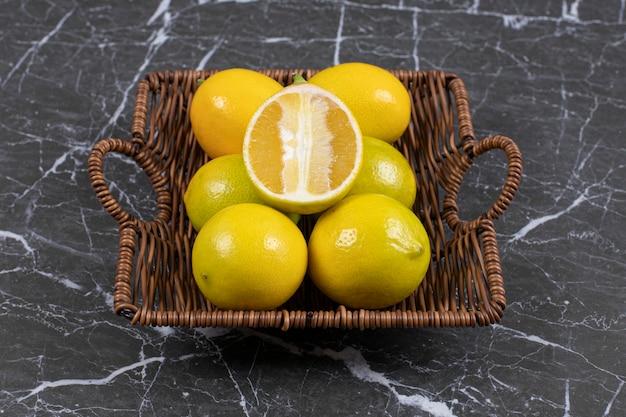 木製のバスケットに新鮮な酸っぱいレモン。