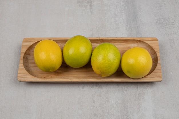 Свежие кислые лимоны на деревянной тарелке.