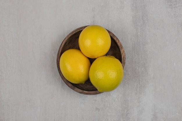Fresh sour lemons in wooden bowl.