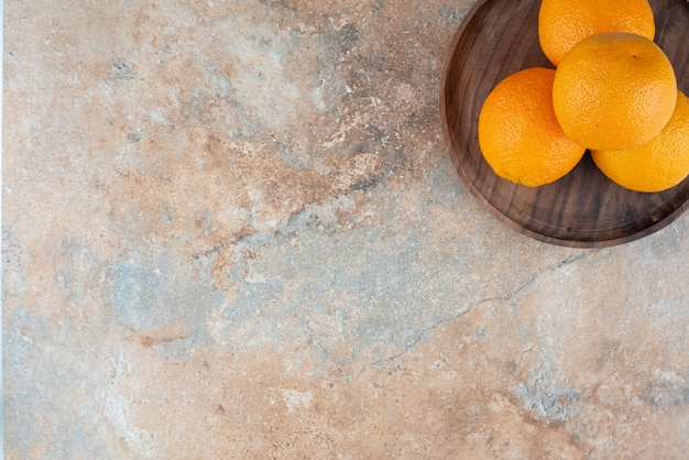 나무 접시에 신선한 신 오렌지입니다.